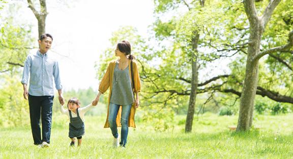 手をつないで歩く家族