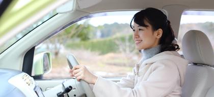 車の運転席でハンドルを握る女性