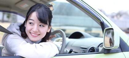 車の運転席から後ろを見る女性